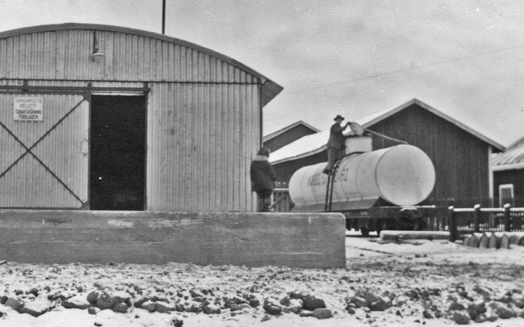 On the left side of the picture, a corrugated sheet metal warehouse on a high concrete foundations, at the corner of which a boy looks at a tank car behind the warehouse, with a man standing on the ladder and opening the hatch.