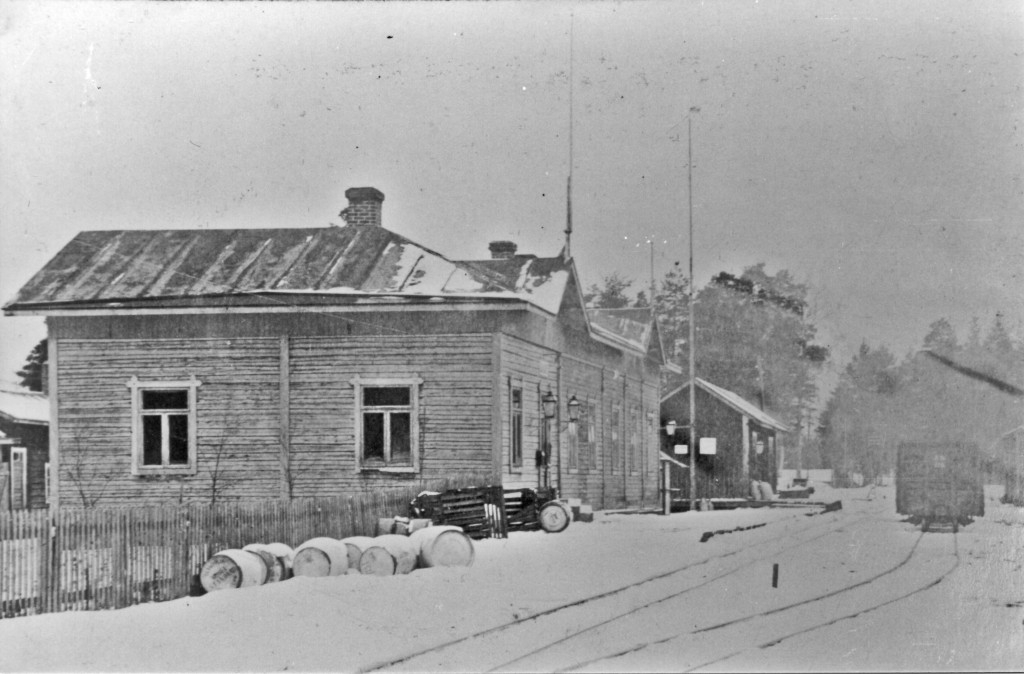 Wooden station building and goods shed in a snowy landscape. The track next to the station is empty, but the next track has a open goods wagon.