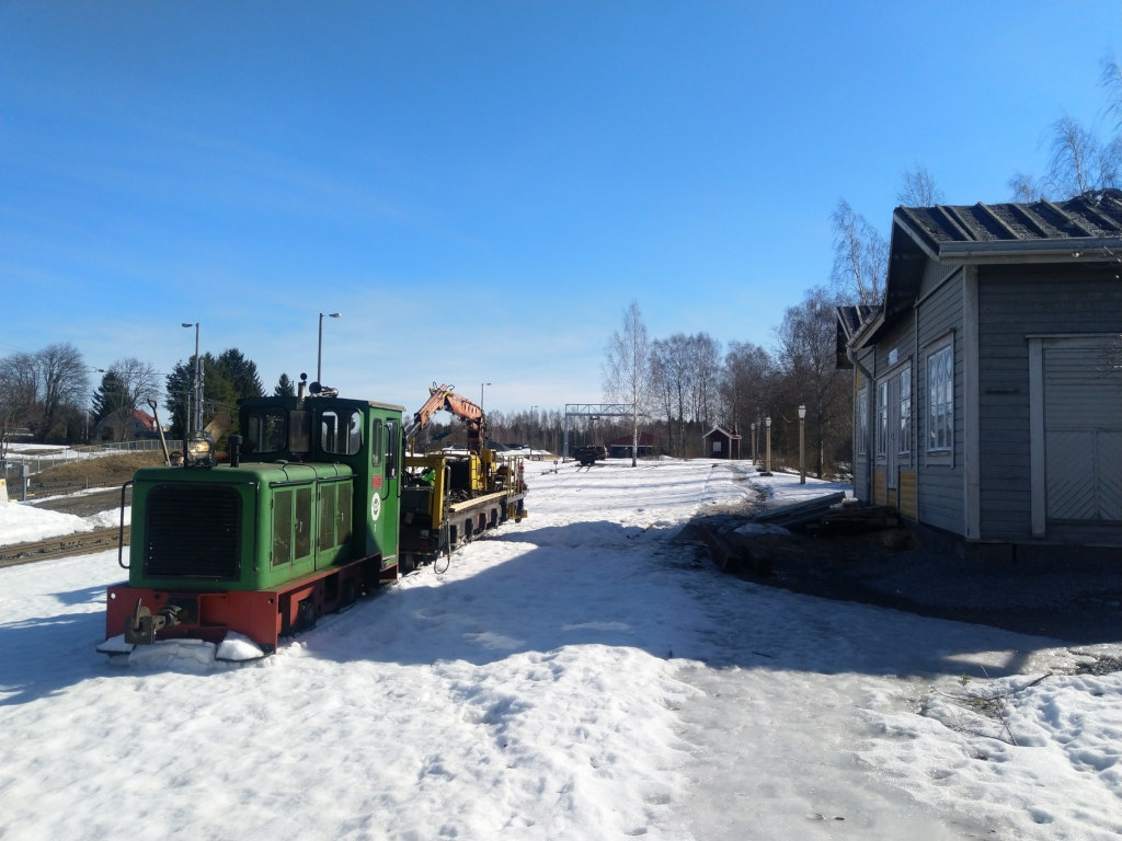 A railway car mounted crane pulled by a small green diesel locomotive stands in front of the snowy Humppila station in the sunshine.