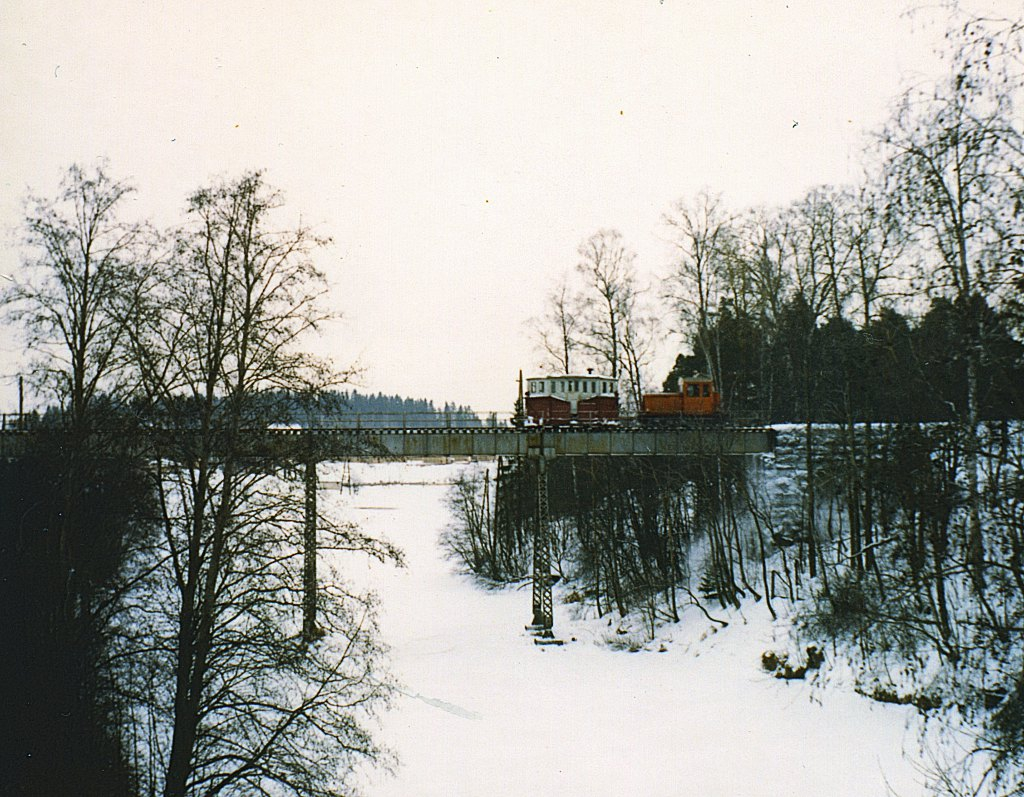 A small diesel locomotive painted orange-yellow with a box snow plow on a high metal girder bridge across the river.