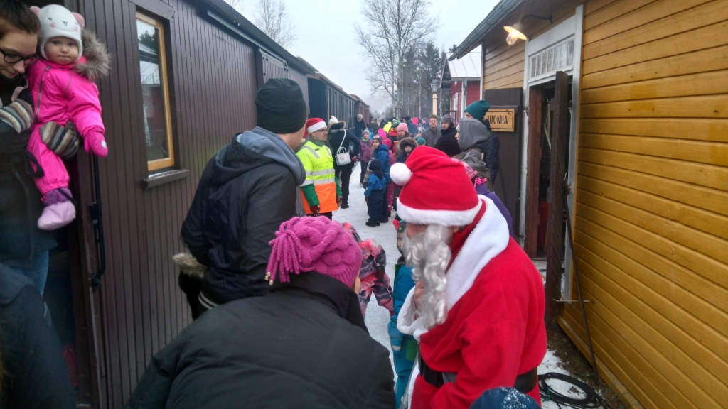 Crowd on the snow-covered platform between the old passenger train and the station. Among the crowd is Santa Claus handing out candies to the kids.