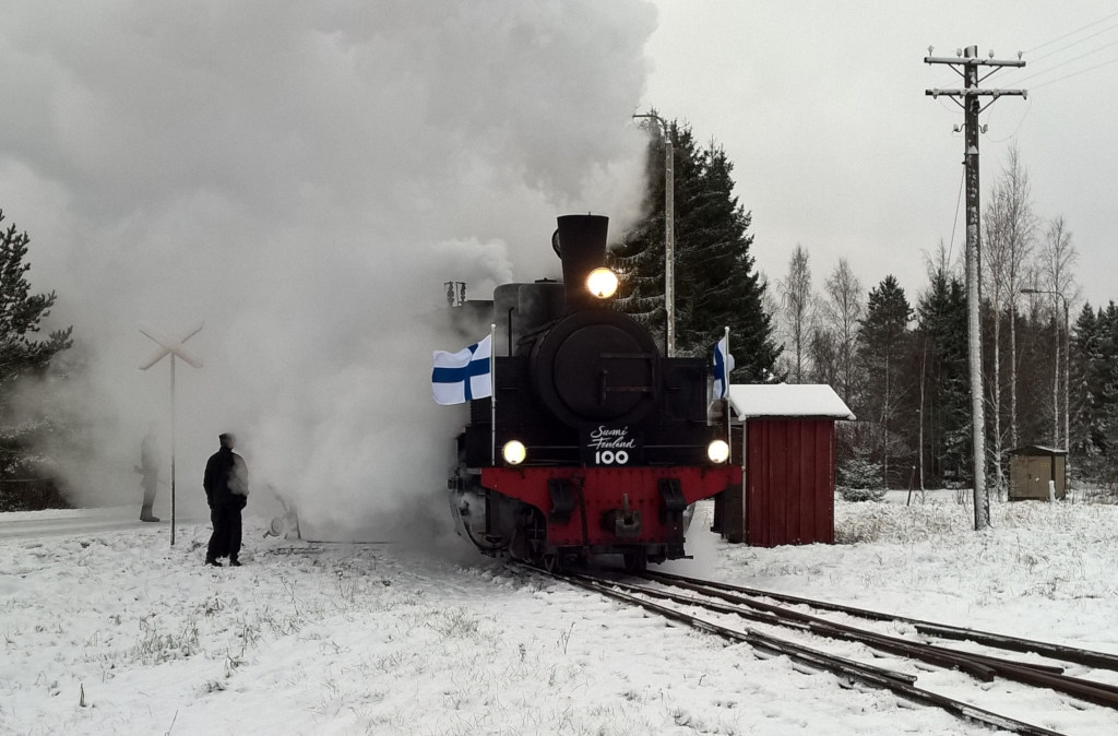 A steam locomotive with Finnish flags flying is diving out of a steam cloud in a snowy landscape.