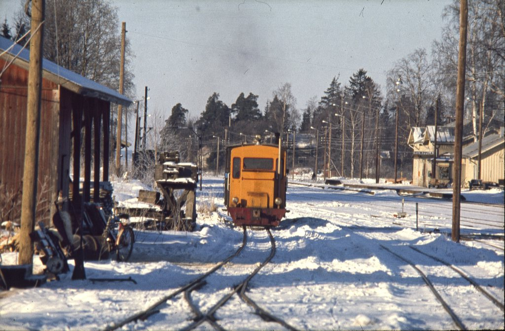 A small diesel locomotive painted orange-yellow in a narrow-gauge yard covered with white snow. On the left a wooden red firewood canopy.