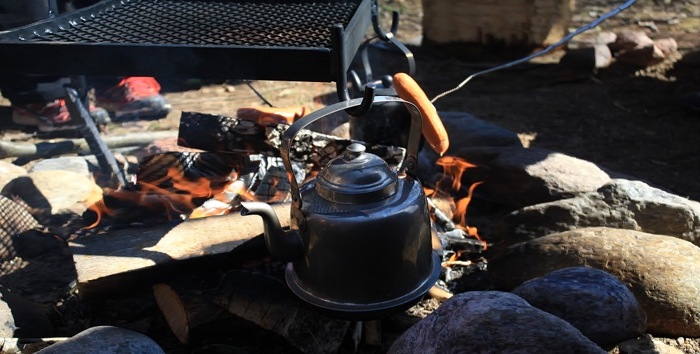 Coffee pot and some sausages on an open fire.