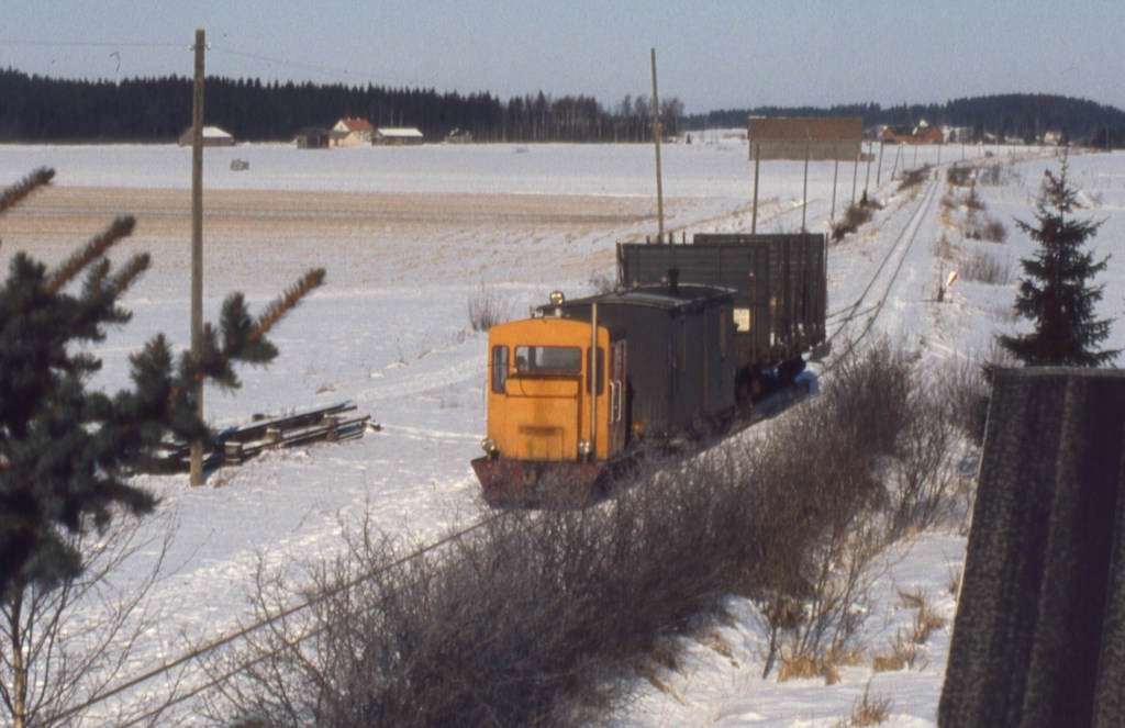 A small diesel locomotive painted orange-yellow pulls two wagons on a narrow-gauge track covered with white snow.