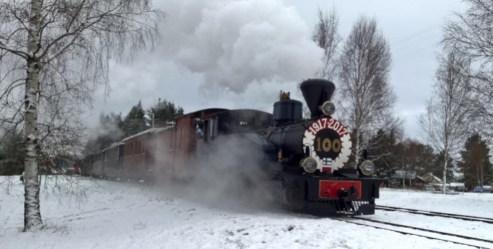 Photo of JR5 steam locomotive at snowy Minkiö station with Finnis flags flying.