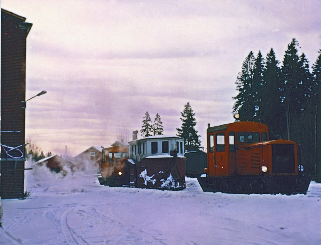 Two orange-yellow diesel locomotives and a box snow plow between them stand on a snowy track next to a red-brick factory building.