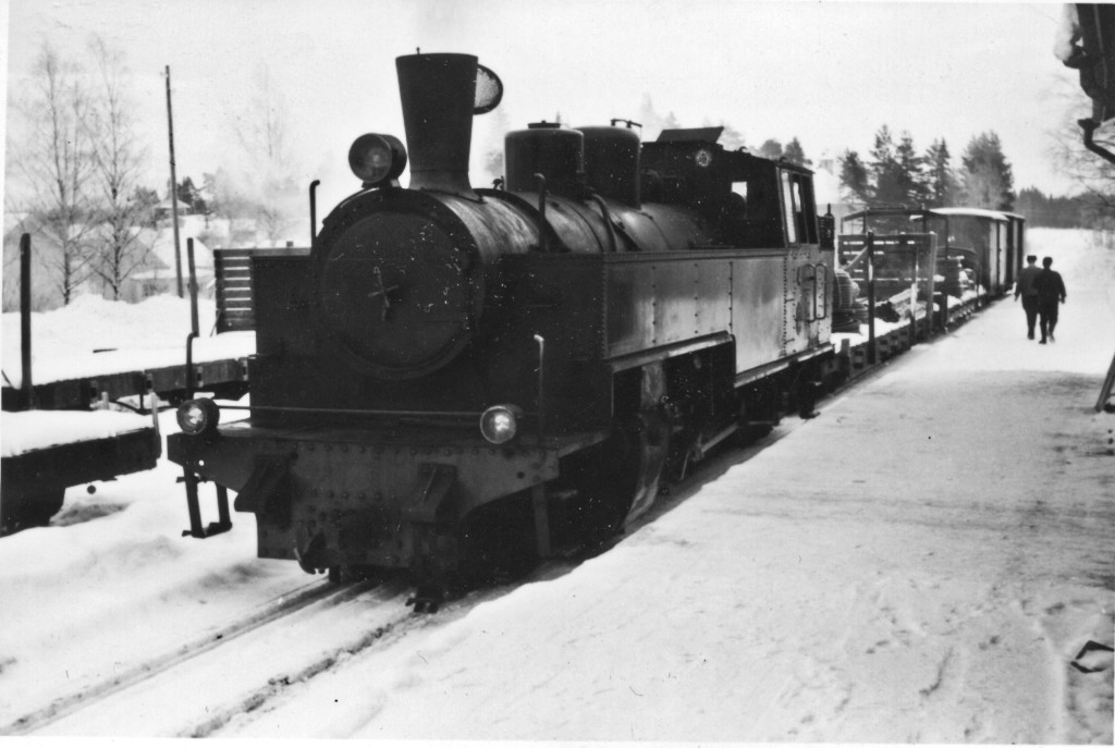 A freight train pulled by a steam locomotive sits next to a snow-covered station platform.