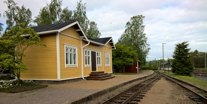 Yellow wooden station building sitting next to narrow gaueg tracks.