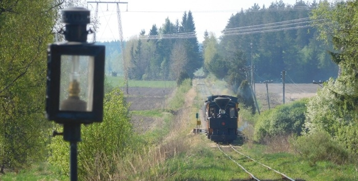 A small steam locomotive is pulling a train towards photographer through green countryside.