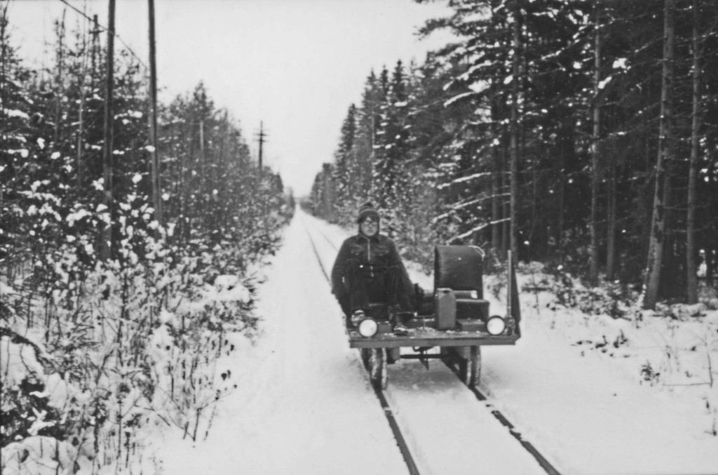An open narrow-gauge motor trolley runs along a track through a snowy forest.