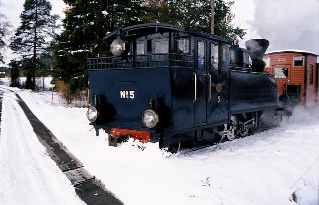 A train pulled by a steam locomotive crossing a snowy level crossing