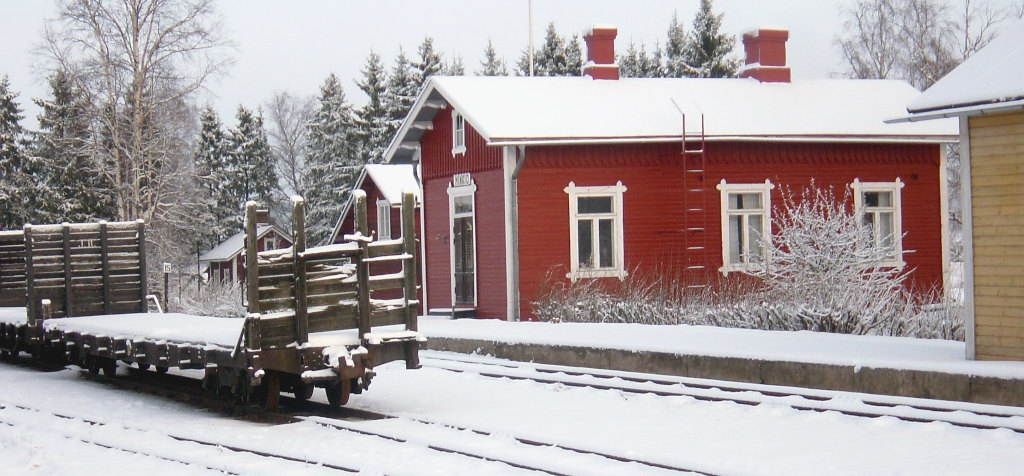 Snowy railway station area. A red station building and a snow-covered yard with an open snow-covered freight wagon.