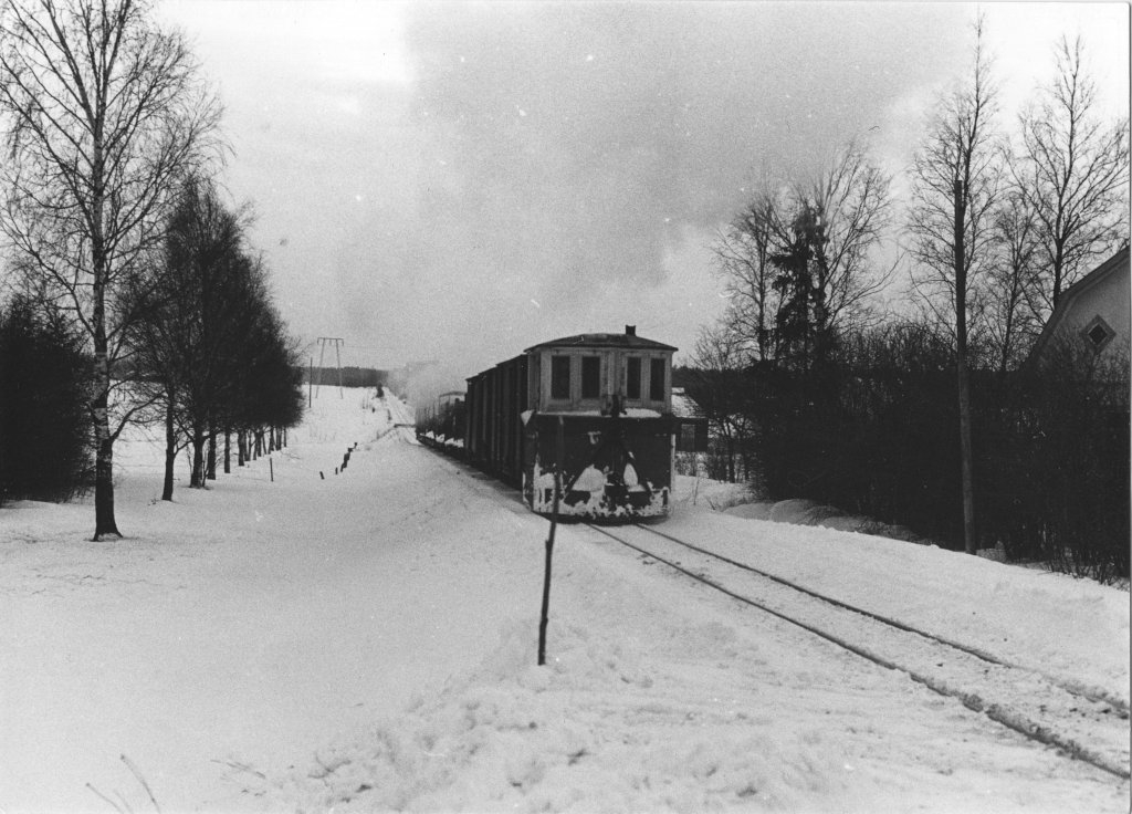 A freight train pulled by a steam locomotive runs away from the photographer in an image taken at a level crossing. The last car of the train is a box snow plow and the landscape is snowy winter landscape.
