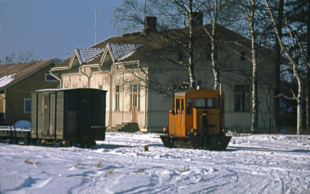 An orange-yellow diesel locomotive runs on a snowy railway yard in front of a wooden station building. The adjacent track has a wooden box car.