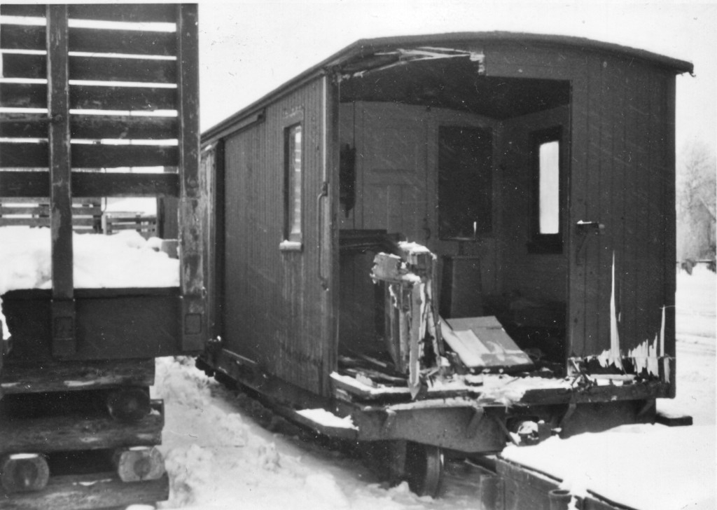 A damaged guard's wagon in a snowy railway yard. The entire front corner of the carriage is gone and through the hole one can see inside of the carriage.