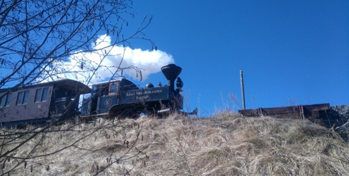 Small steam locomotive is pulling a passanger train on high embankment in sunny weather.