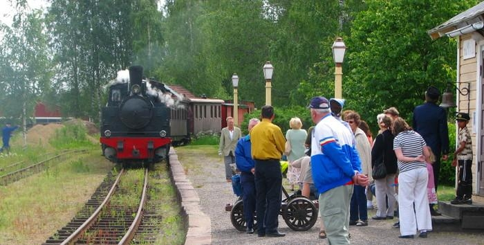 A train pulled by a steam locomotive arrives at station. The platform is full of people waiting for the train.
