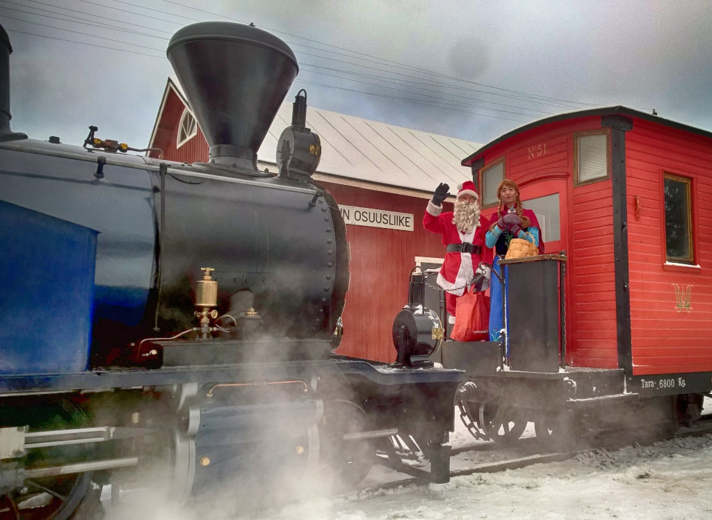 Santa Claus  stands on the end platform of a red guard's van. The van is pulled by a steam locomotive. In the background, a wooden red cooperative warehouse building stands.