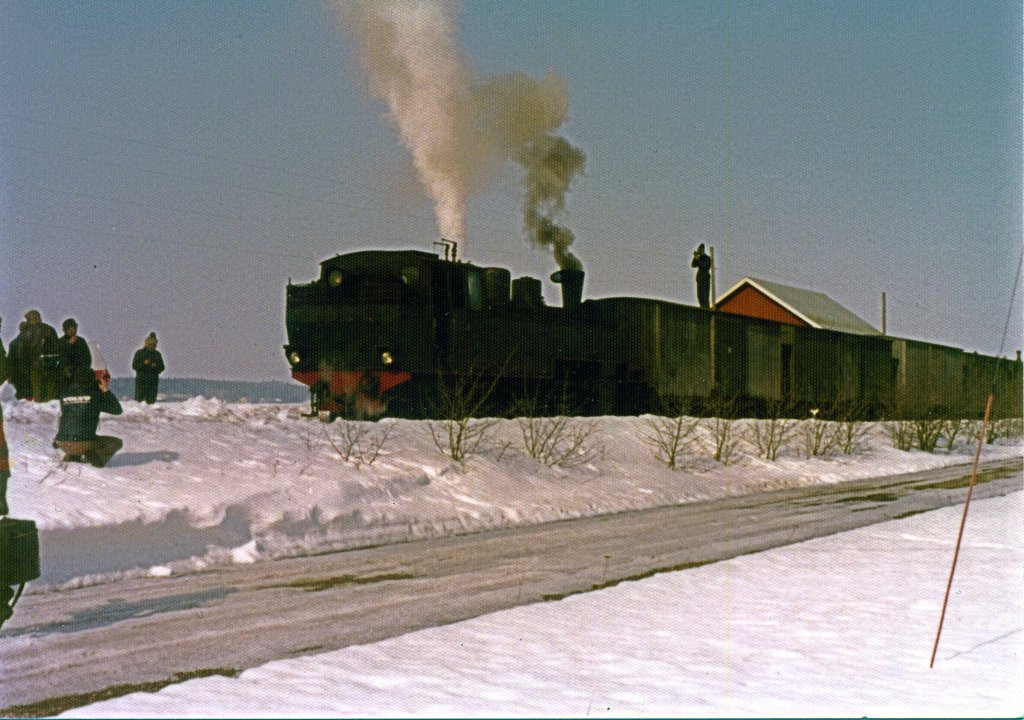 A freight train pulled by a steam locomotive stands in a snowy yard in the sunshine. There are a lot of people around the train.