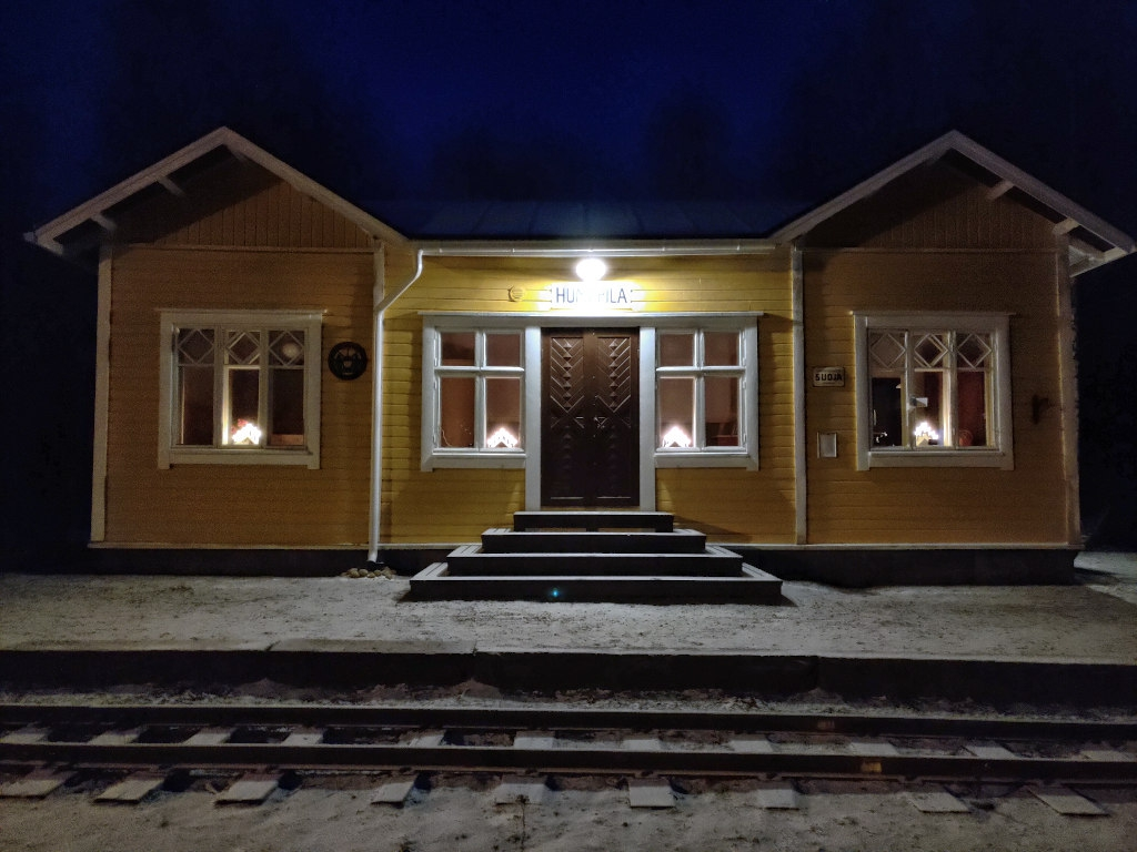 Yellow wooden station building with Christmas candles on windows. There is a small layer of snow on the ground.